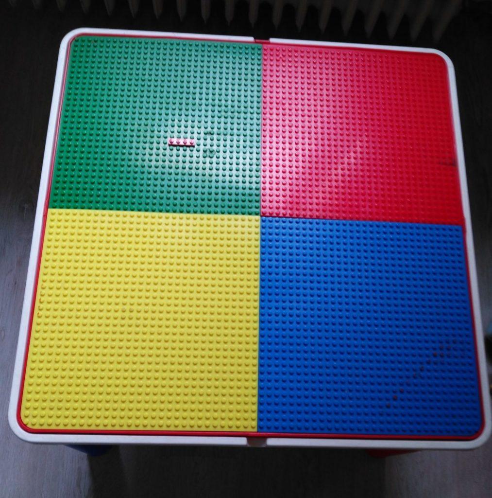 Esta mesa pensada para jugar con piezas de construcción era ideal para usarla como base para la mesa de luz. Tiene una tapa reversible lisa / con base para fijar piezas, y un hueco debajo.
