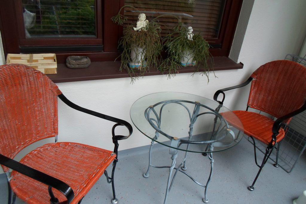 Las sillas y la mesa de cristal tras la renovación del balcón