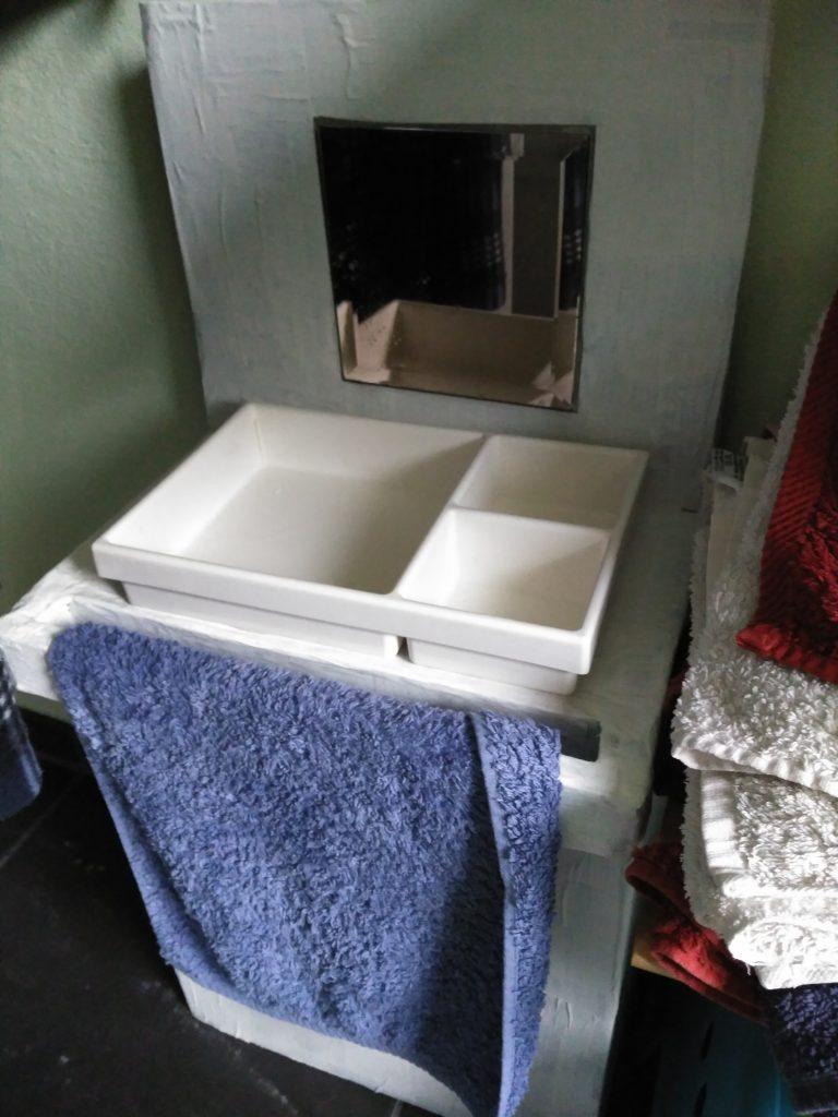 Mini Lavabo adaptado a los niños inspiración Montessori hecho con cajas y paneles de Cartón, con toallero y una bandeja con separaciones a modo de pileta.