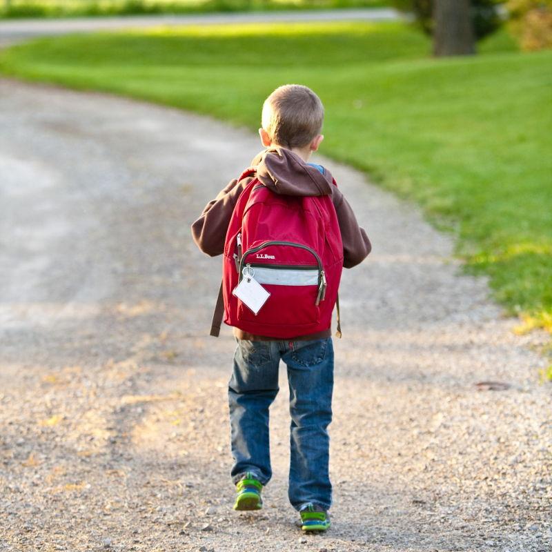 Niño con mochila yendo solo