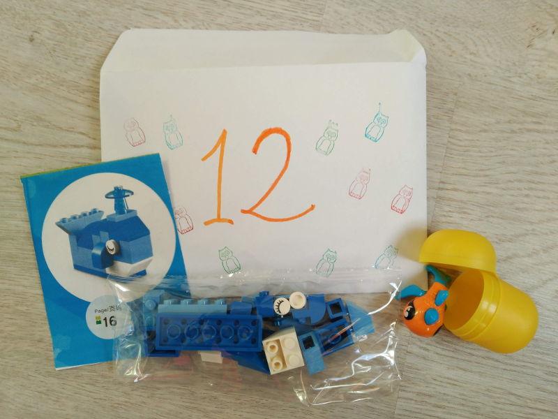 Calendario de Adviento DIY - Regalitos a partir de cajas de piezas de lego y relleno de huevos sorpresa - En la imagen se ve un sobre con el número 12, una bolsa con piezas de Lego, la imagen de guía para montar una ballena y un huevo sorpresa con un pez.