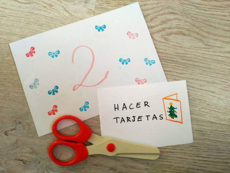 """Calendario de Adviento DIY - Manualidades - Sobre del día 2: Preparar tarjetas de Navidad para enviar a familiares y conocidos. En la imagen una nota con el texto """"hacer tarjetas"""" y unas tijeras."""