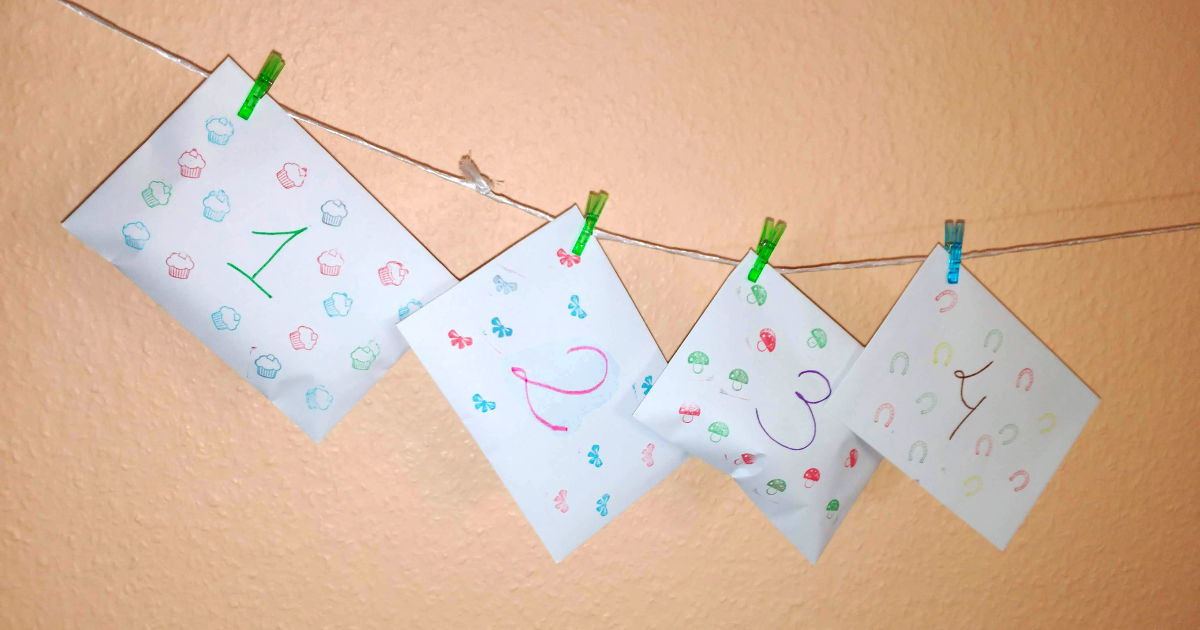 Calendario de Adviento DIY - Hecho con sobres normales, decorados con números y sellos. Colgados de una cuerda con pinzas. En la muestra se ven los sobres de los primeros 4 días.
