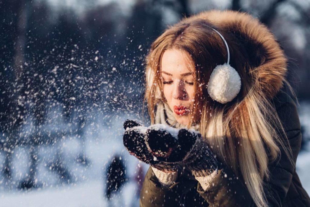 Prepararse para el invierno en Alemania - Imagen ilustrativa chica requetemona con ropa de abrigo en la nieve soplando unos copos de sus manos