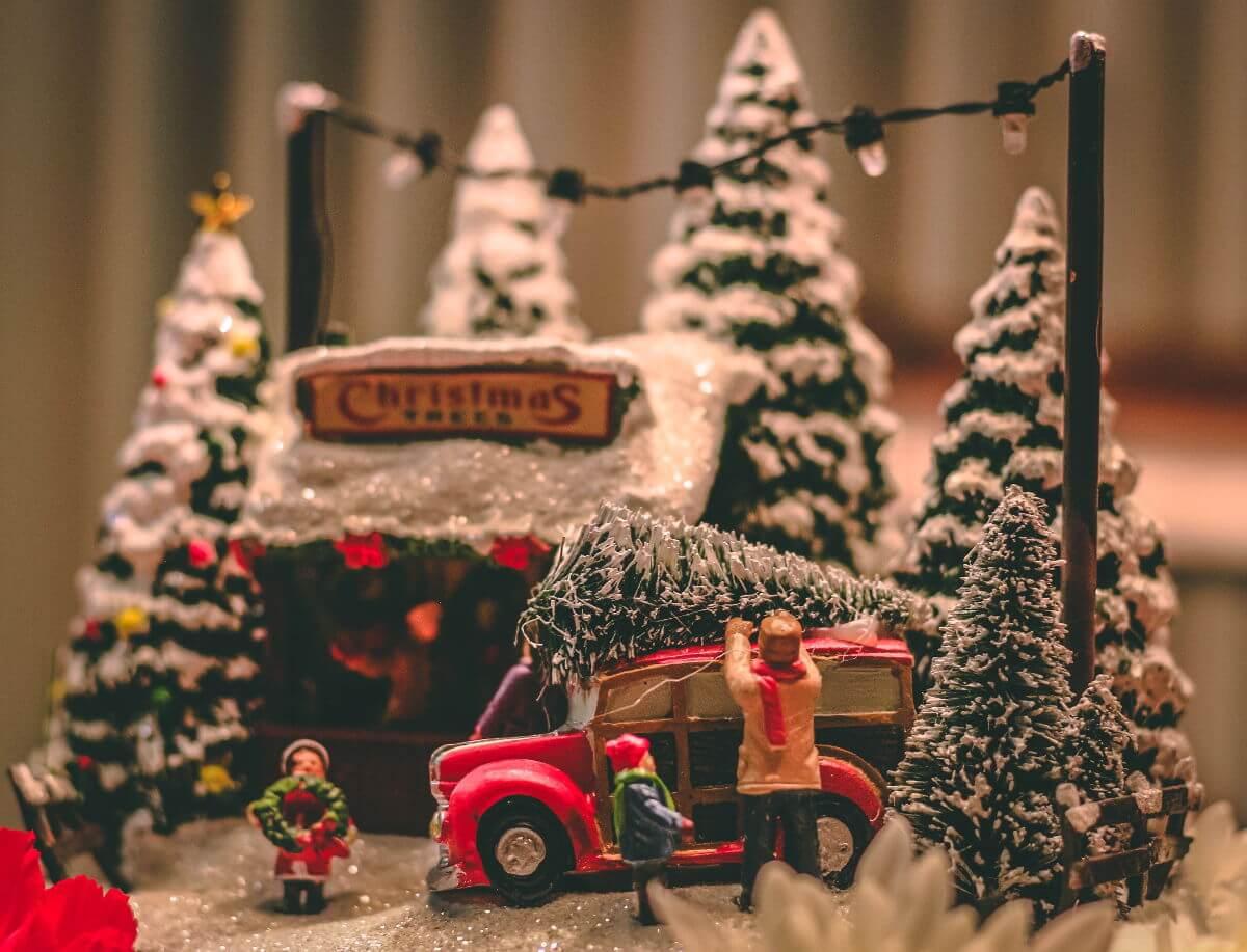tradiciones navideñas alemania - Imagen ilustrativa - figuras comprando un árbol de navidad en un mercado y subiéndolo al coche