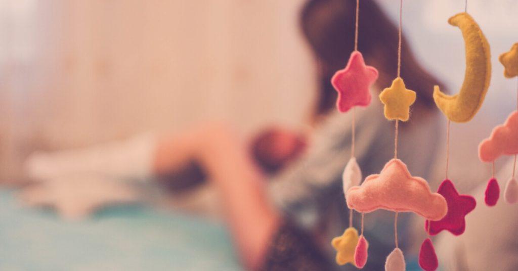 Las hormonas en el postparto - imagen ilustrativa, madre amamantando a un bebé en el fondo, en el frente un colorido móvil de bebé.