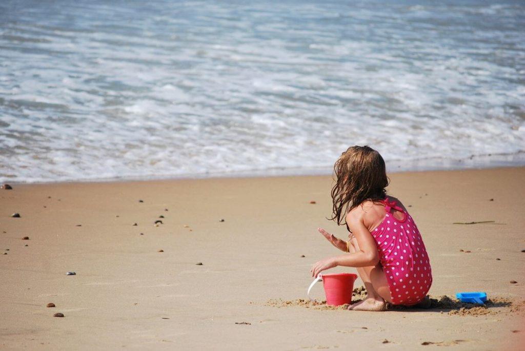 verano con niños - Una niña jugando en la playa