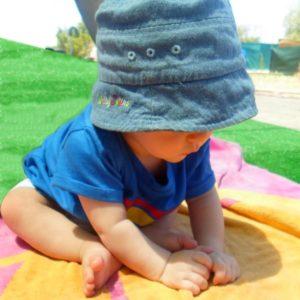 Crema solar para bebés - Imagen ilustrativa, bebé jugando al sol.