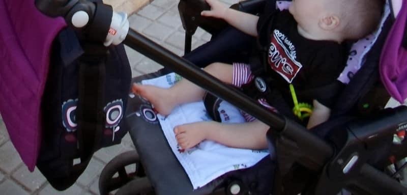 Ojo con las piernas cuando va el bebé con el carro, mejor poner crema solar. Imagen ilustrativa bebé paseando en carro.