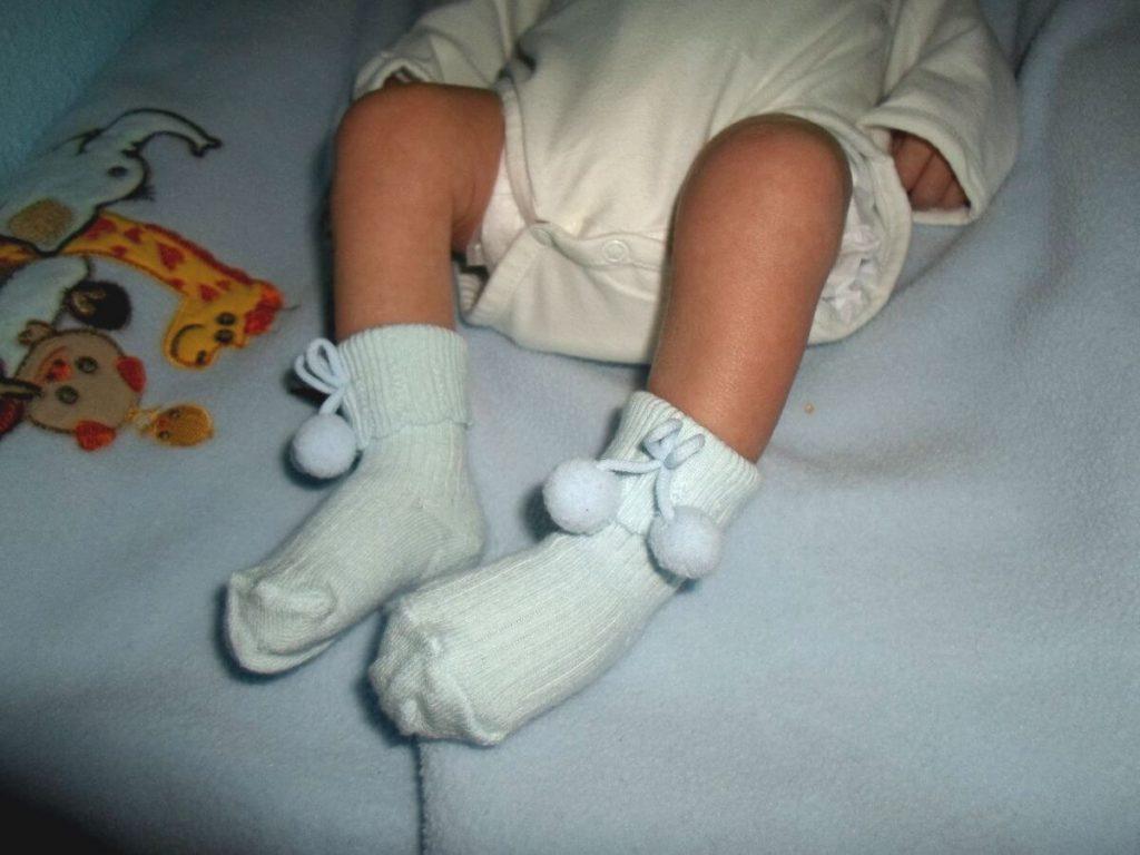 Calcular cuándo nacerá el bebé - Imagen ilustrativa, foto de pies de bebé recién nacido de 15 días con calcetines azul celeste.