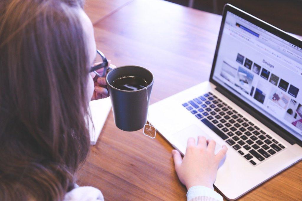 Trabajar desde casa - Imagen ilustrativa, mujer trabajando en un ordenador mientras toma un té
